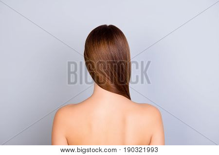Close Up Cropped Back View Photo Of Young Brown Haired Girl Standing On Light Blue Background. She H