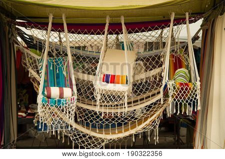 OTAVALO, ECUADOR - MAY 17, 2017: Andean traditional hammock textile yarn and woven by hand in wool, colorful fabrics background.