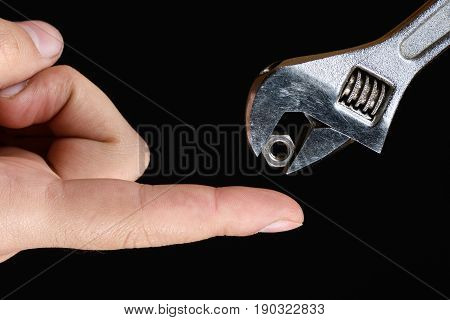 The Spanner Wrench Holds The Nut And Give It In Hands On Black Background Isolated