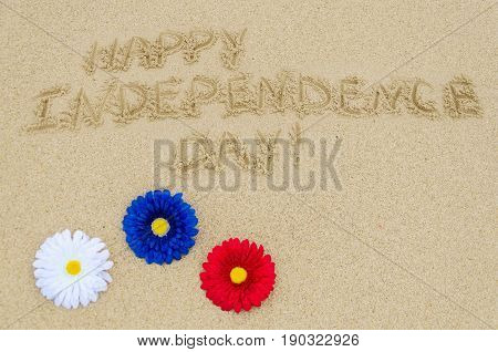 Independence USA background with red blue and white decorative flowers on the sandy beach near ocean