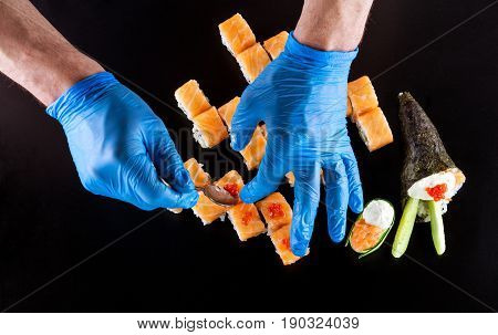 Cropped view of chef preparing sushi over black background