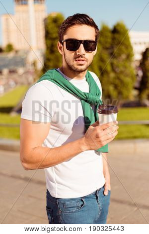 Harsh Young Brunete Guy Is Having A Coffee And Walking In The City Outdoors,  In Casual Comfortable