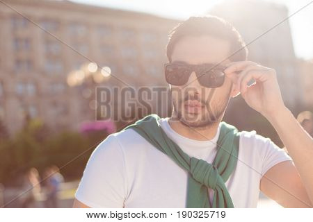 Close Up Of A Harsh Young Brunete Guy, Walking In The City Outdoors,  In Casual Comfortable Outfit,