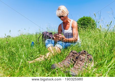 Mature Woman With A Phone At A Hiking Rest
