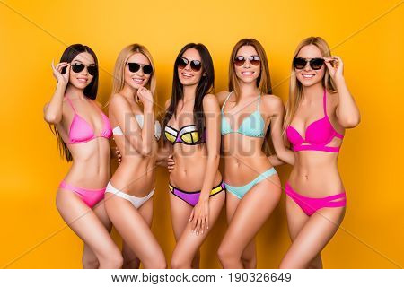 Hot Brunette, Blond And Brown-haired Girls Are Posing  In Colorful, Trendy, Fashionable Swimming Sui