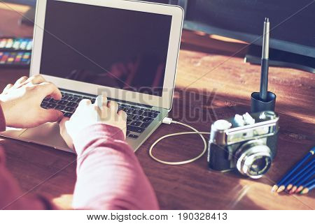 Creative young man his office / agency working with movie camera - instagram style analog film look