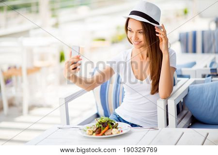 Young Cheerful Lady Is Having Lunch On A Summer Open Air Light Terrace Outdoors. She Is In A Casual
