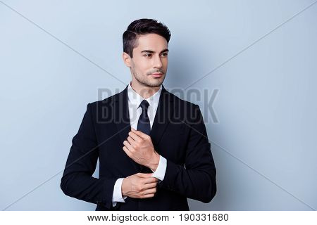 Young Attractive Brunete Businessman Banker Is Standing On The Pure Light Background. He Looks Stunn