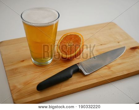 A cold glass of beer with orange slice and kitchen knife on a cutting board.