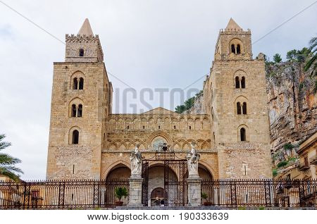 The facade of the Cathedral-Basilica of Cefalù features two large Norman towers with mullioned windows - Sicily Italy