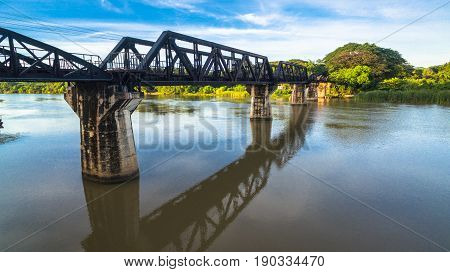 The train is passing through the Death Railway Bridge over the River Kwai in Kanchanaburi. During World War Two Japan constructed railway from Thailand to Buma This is now know the Death Railway.