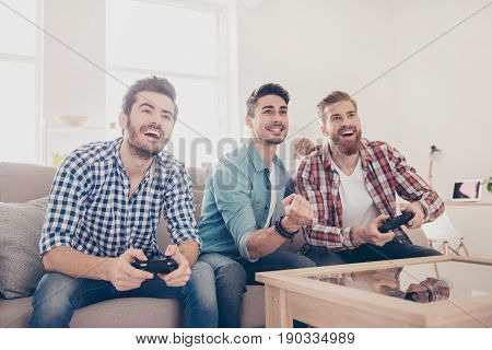 Who Will Win? Competition Of Guys Playing Car Race. Excited Friends Are Playing Games  Indoors At Ho