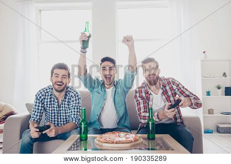Yes! Team Of Winners! Happy Joyful Men Are Sitting On Sofa And Playing Video Games With Beer And Piz