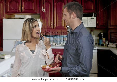 Wife or girlfriend stealing french fries from her boyfriend or husband