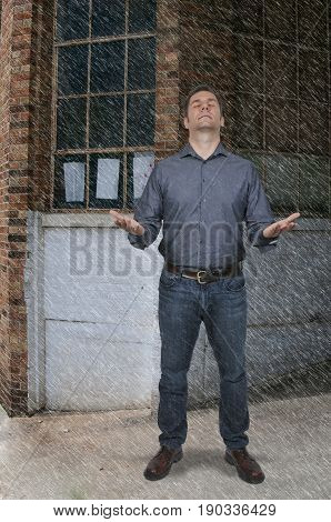Attractive handsome American or European man standing in the rain with outstretched arms