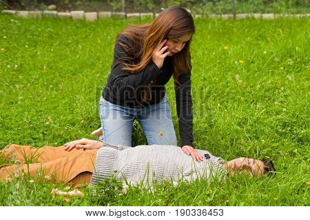 Beautiful woman giving first aid to a handsome young man and using her cellphone to call the ambulance, cardiopulmonary resuscitation, in a grass background.