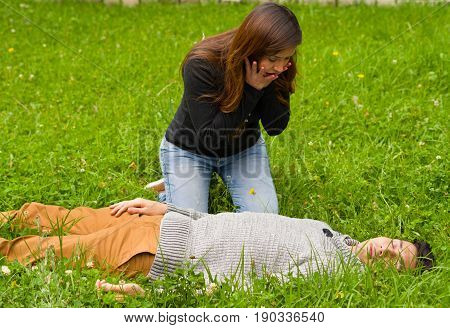 Surprised beautiful woman watching a handsome young man that is over a grass, cardiopulmonary resuscitation concept, in a grass background.