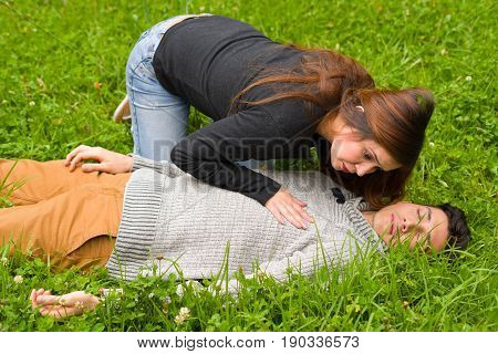 Young beautiful woman checking a handsome young man if he still breathing, cardiopulmonary resuscitation concept, in a grass background.