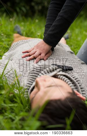 Close up of a beautiful woman giving first aid to a handsome young man, cardiopulmonary resuscitation, in a grass background.