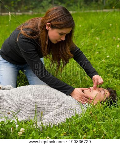 Beautiful women giving first aid, cardiopulmonary resuscitation, in a grass background.