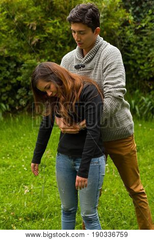 Handsome young man well dressed doing the first aid to a beautiful woman, cardiopulmonary resuscitation concept, in a backyard background.