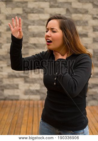 Young beautiful woman feeling bad and gripping her neck with one hand and asking for help with her other hand, cardiopulmonary resuscitation concept, in a blurred background.