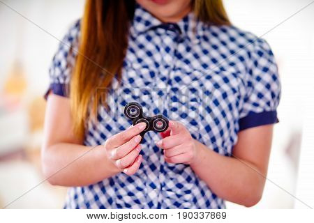 Young smiling woman holding a popular fidget spinner toy in her hand.