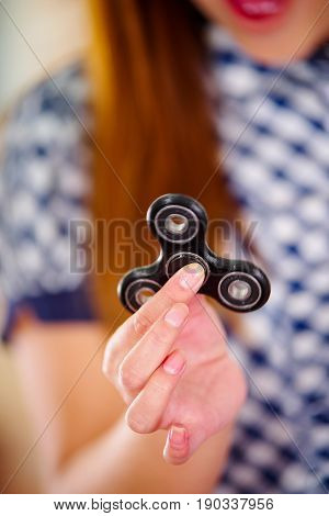 Close up of a young woman holding a popular fidget spinner toy in her hand.