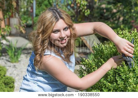 Smiling attractive teenage girl is cutting a shrub with garden shears outdoors. The girl is looking at the camera.