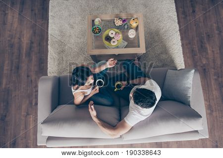 Weekend Together. Sunday Morning.  Top Up Of Beautiful Couple Is Sitting On Beige Big Sofa And Drink