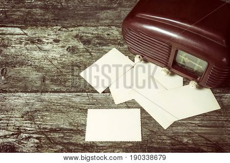High angle view of the vintage photo of old radio standing on the old wooden desk. Blank old photos are placed in front of the radio. Suitable for your text. All potential trademarks are removed and blurred.