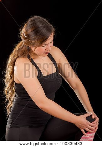 Beautiful young attractive sport woman holding injured knee suffering pain, in black background.