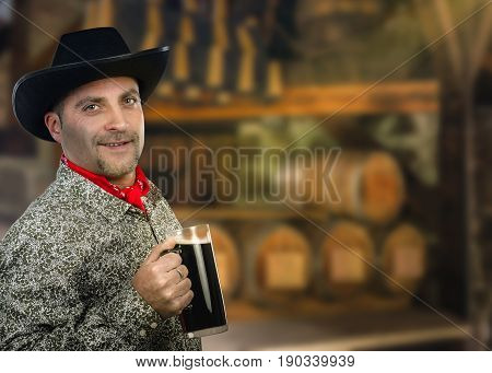 Friendly cowboy holding big glass of porter beer. Man wears black hat, red scarf and white gray patterned shirt with long sleeve. Mid shot on blurred indoors background of pub interior