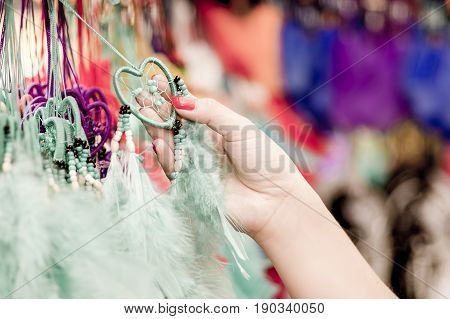 OTAVALO, ECUADOR - MAY 17, 2017: Close up of a woman holding a catchdreamer in her hand, in colorful market background.