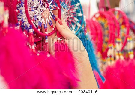OTAVALO, ECUADOR - MAY 17, 2017: Close up of a woman holding a pink catchdreamer in her hand, in colorful market background.
