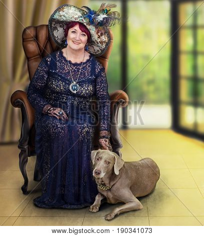 Older woman in tapestry hat with feathers posing with weimaraner dog. Lively lady in dark guipure dress sits in wooden armchair. The dog lies next on yellow floor. Vertical shot on blurred interior background
