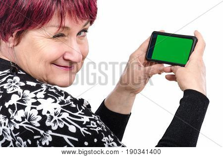 Lively older woman holding mobile phone with chroma key screen winks at the camera on white background. Concept of online dating for senior people