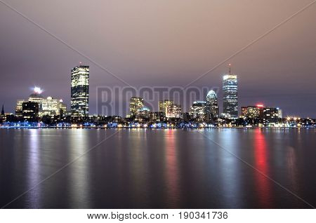 The Boston Massachusetts skyline at night reflected on the water.