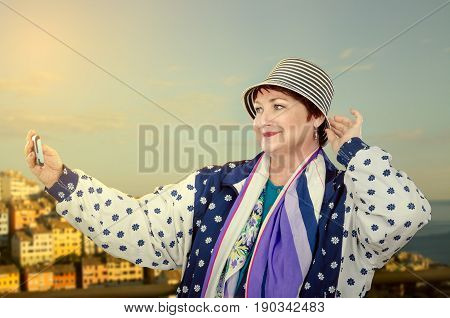 Active aged woman in colorful white blue jacket takes selfie photo with mobile phone on blurred background of European city is flooded by sunrise. Elderly traveling concept
