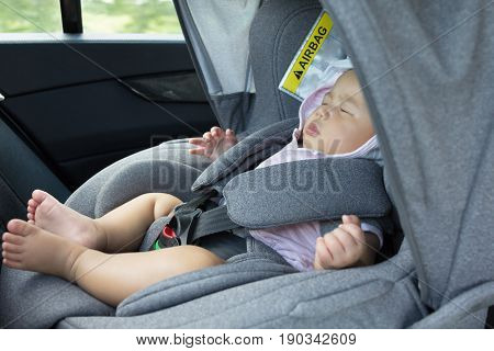 Close Up Asian cute newborn baby sleeping in modern car seat. Child new born traveling safety on the road. Safe way to travel fastened seat belts in a vehicle with young kids. Trip with an infant.