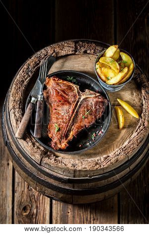 T-bone Steak With Chips On Old Barrel