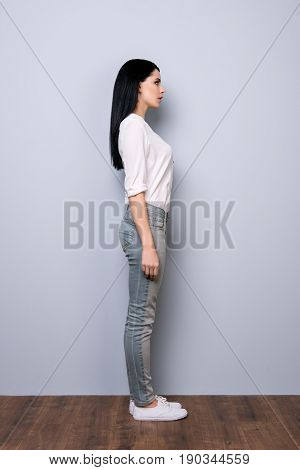 Full Size Profile View Of Brunette Girl In Casual Outfit And White Shoes On Pure Grey Background. Mo