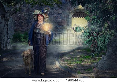 Older fairy with lamp walking her weimaraner dog in dark park. Woman wears a black guipure clothing and big tapestry hat with feathers. There is rear arched entrance in medieval stone wall on background. Horizontal shot