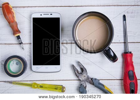Smartphone, Coffee Cup And Equipment Repair On The White Wooden Background.
