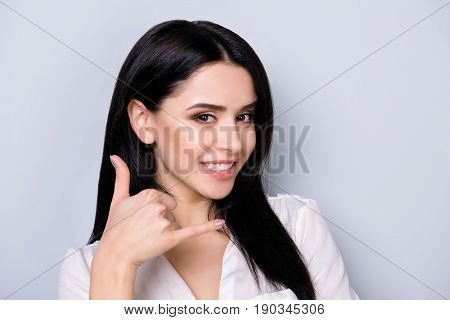 Cheerful Brunette Young Girl With Beaming Smile Is Gesturing To Call Her With A Hand. She Is Wearing