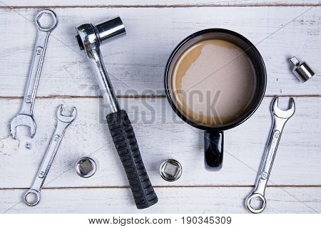Coffee Cup And Equipment Repair On The White Wooden Background