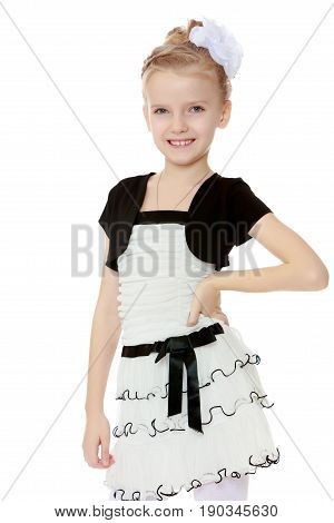 Beautiful little blonde girl dressed in a white short dress with black sleeves and a black belt.The girl is thrusting the leg.Isolated on white background.