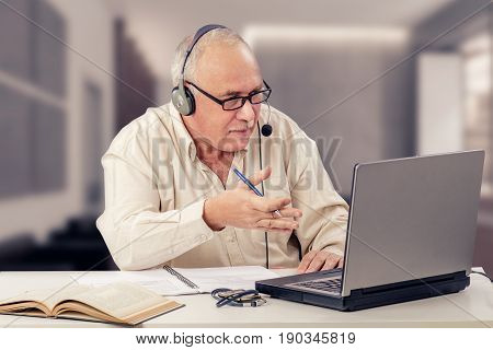 Balding retired man works as freelancer in internet from home office. Older man in headset explains emotionally sitting in front of the laptop computer.  Horizontal indoors mid shot on blurry background