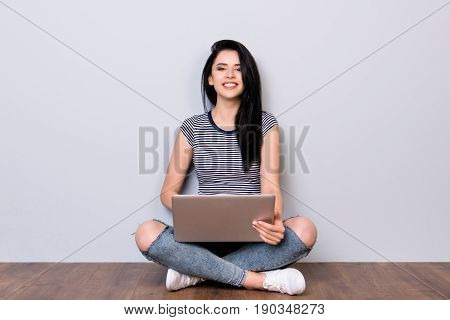 Young Cheerful Brunette Is Sitting On The Wooden Floor With Crossed Legs And Is Typing On Her Laptop