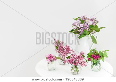 Vases with pink and purple blooming spring flowers on a round table.